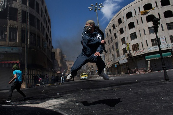A Palestinian throws a stone towards Israeli forces